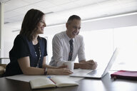 Smiling businessman and businesswoman working at laptop in office meeting - HEROF23279