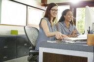 Smiling businesswomen working at computer in office - HEROF23291
