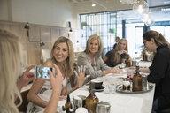Smiling women friends getting gel manicures, posing for selfie in nail salon - HEROF23303