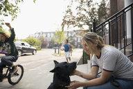 Smiling woman with dog on neighborhood sidewalk - HEROF23318