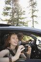 Smiling woman using digital camera in car, enjoying road trip - HEROF23342