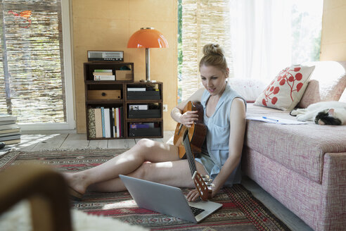 Woman playing guitar, taking online lessons at laptop on living room floor - HEROF23375