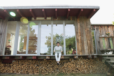 Young man using laptop on wood cabin patio above firewood - HEROF23378