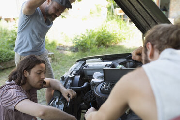 Young male friends fixing car engine - HEROF23390