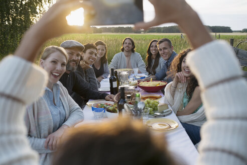 Woman with camera phone photographing friends enjoying garden dinner party in rural yard - HEROF23396