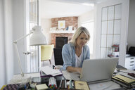 Woman using laptop in home office - HEROF23402