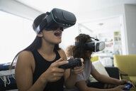 Teenage girl friends playing video games with virtual reality simulators in living room - HEROF23414