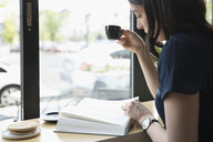 Woman reading book and drinking espresso coffee at cafe window - HEROF23441