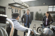 Bikers talking at motorcycles in parking lot - HEROF23474