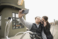 Biker couple with camera phone taking selfie on motorcycle in parking lot - HEROF23477