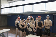 Attentive swimmers standing and listening in swimming practice - HEROF23492