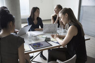 Businesswomen reviewing, discussing data in conference room meeting - HEROF23513