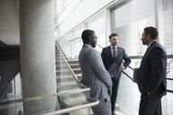 Businessmen talking on office stairs - HEROF23567