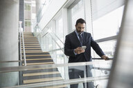 Businessman texting with cell phone on office stairs - HEROF23570