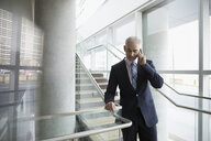 Businessman talking on cell phone on office stairs - HEROF23579