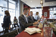 Businessmen working at laptops at diner counter - HEROF23594
