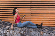 Young woman sitting on a wall listening music with smartphone and headphones - KKAF03114