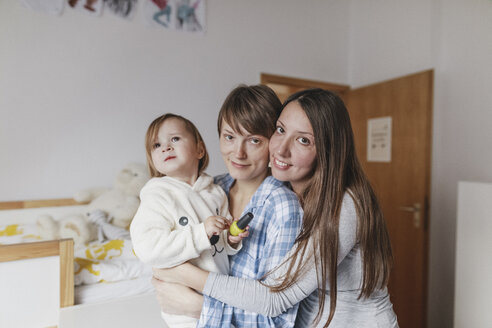 Portrait of happy lesbian couple embracing daughter at home - KMKF00760