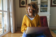 Young woman sitting on chaiselongue using laptop at home - KIJF02273