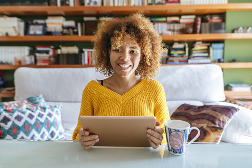 Portrait of smiling young woman with curly hair using tablet at home - KIJF02279