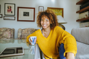 Portrait of happy young woman with curly hair holding mug at home - KIJF02282
