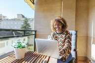 Young woman with curly hair sitting on balcony using laptop - KIJF02291