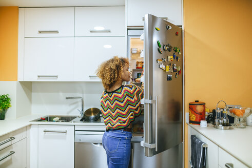 Young woman with curly hair opening the fridge in kitchen - KIJF02297