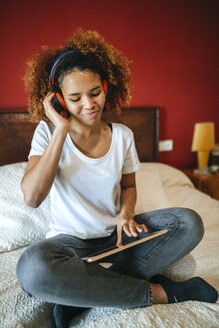 Spain, Andalusia, cadiz, Jerez,  Woman listening to music with tablet sitting on the bed - KIJF02300