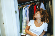 Young woman with curly hair at home looking at clothing in her wardrobe - KIJF02321