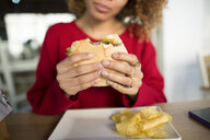 Close-up of woman's hands holding a hamburger - KIJF02324