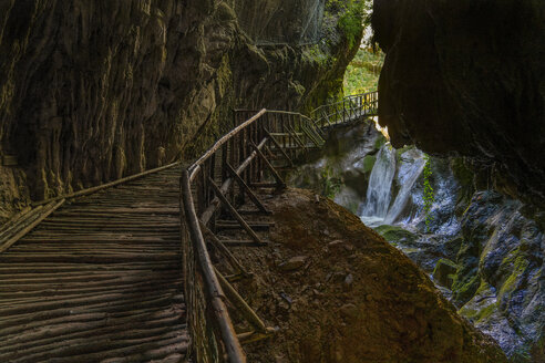 Italy, Veneto, Caglieron caves, Waterfall and wooden trail in the caves - LOMF00801