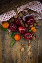 Wickerbasket, red apples, tangerines, hazelnuts and walnuts on dark wood - LVF07789