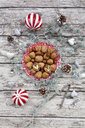 Walnuts on a plate with Christmas decoration, overhead view - LVF07798