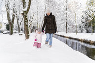 Happy mother walking with daughter at a moat in winter landscape - DIGF05863