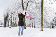 Happy mother playing with daughter in winter landscape - DIGF05866