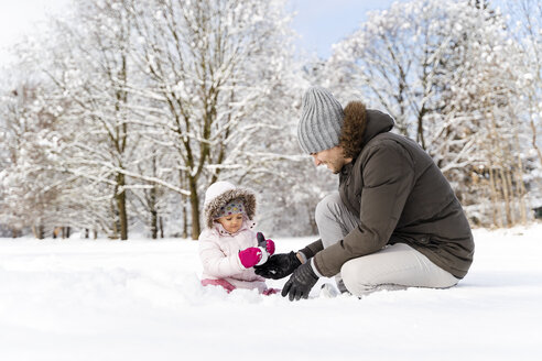 Happy father playing with daughter in winter landscape - DIGF05887