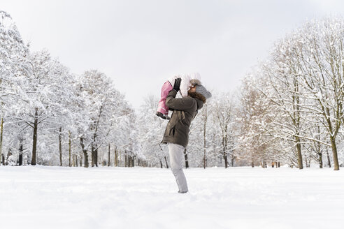 Happy affectionate father carrying daughter in winter landscape - DIGF05893