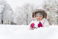 Cute little girl playing with snow in winter - DIGF05896