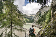 Switzerland, Valais, woman on a hiking trip from Blatten to Riederalm  at a reservoir - DMOF00108