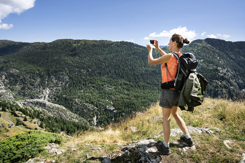 Switzerland, Valais, woman taking picture during a hiking trip in the mountains from Belalp to Riederalp - DMOF00111
