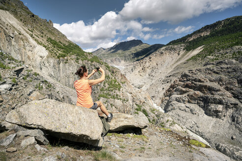 Switzerland, Valais, woman taking picture during a hiking trip in the mountains at Aletsch Glacier - DMOF00114