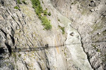 Switzerland, Valais, shadows of two people on a swinging bridge above a gorge - DMOF00117