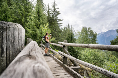 Switzerland, Valais, woman standing on a wooden bridge during a hiking trip on the Massaweg in the mountains - DMOF00120