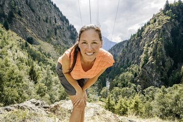 Switzerland, Valais, portrait of happy woman on a hiking trip in the mountains on the Massaweg - DMOF00126