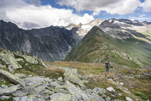 Switzerland, Valais, woman on a hiking trip in the mountains towards Foggenhorn - DMOF00132