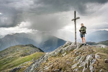 Switzerland, Valais, woman on a hiking trip in the mountains at Foggenhorn summit - DMOF00135
