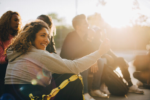 Happy woman taking selfie on smart phone while sitting with friends at park - MASF11375