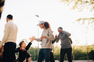 Happy friends greeting each other at skateboard park against clear sky - MASF11378