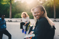 Portrait of smiling teenage girl sitting with friends at skateboard park - MASF11387