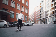 Full length of young man skateboarding on street against buildings in city - MASF11402